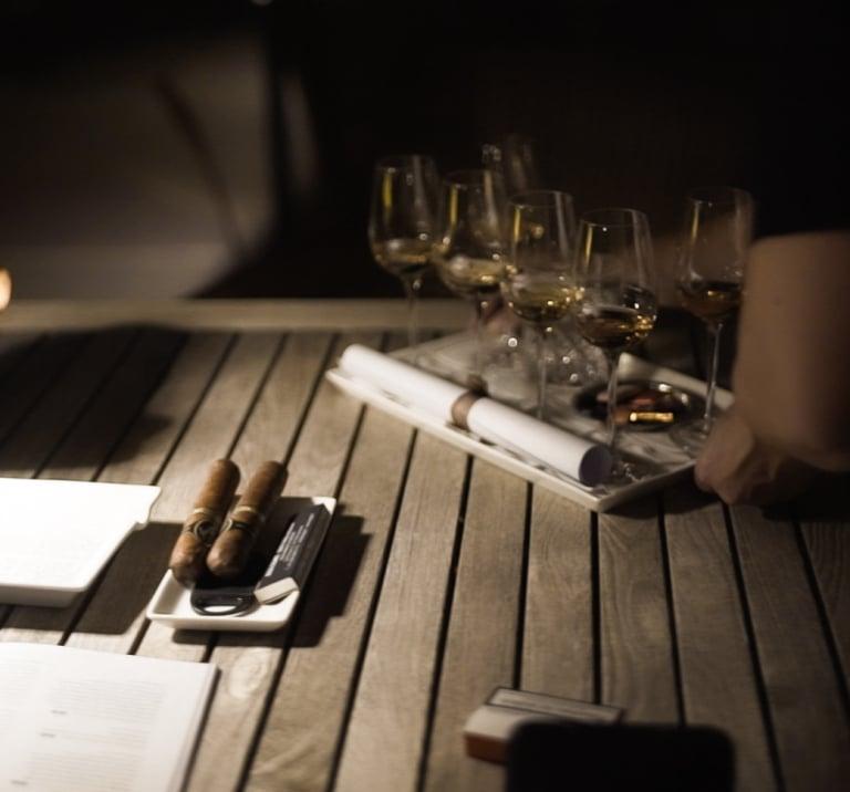 Holztisch mit Gläsern und Zigarren