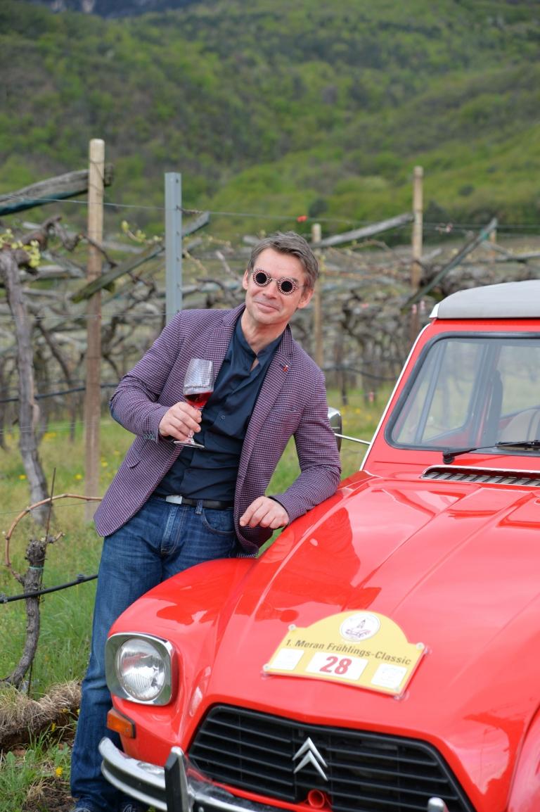 Herr mit Weinglas lehnt auf Auto