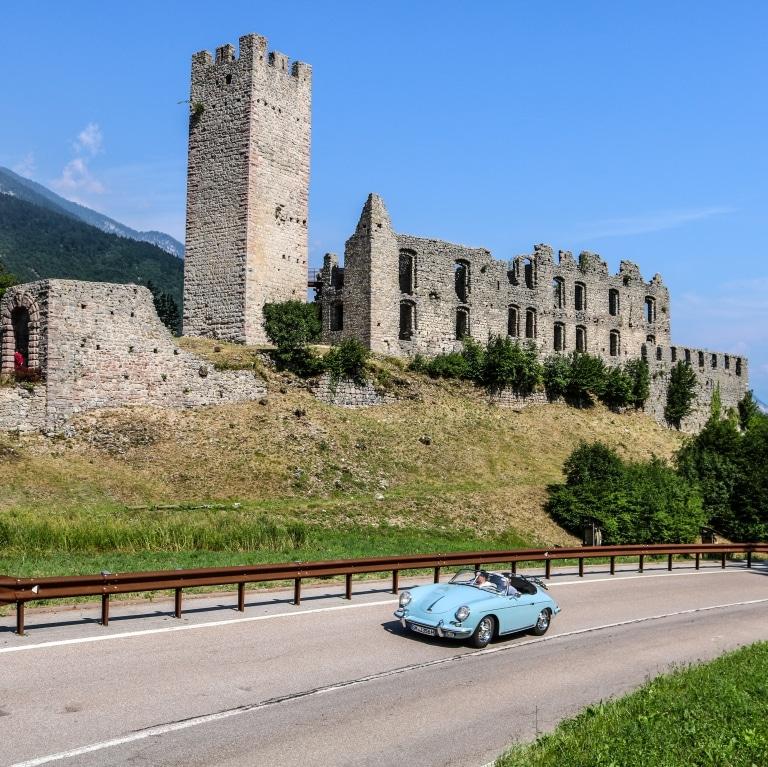 Blaues Auto im Vordergrund, Burgruine im Hintergrund